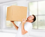 Man carrying carton heavy box. New home and post delivery concept - man carrying carton heavy box Stock Photos
