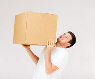 Man carrying carton heavy box Stock Photo