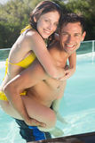 Man carrying cheerful woman by swimming pool Royalty Free Stock Images