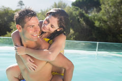 Man carrying cheerful woman by swimming pool Stock Images