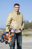 Man carrying children bike Stock Images