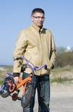 Man carrying children bike stock images