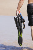Man carrying diving gear on beach. Snorkel, goggles and flippers carried by a man on the beach Stock Image
