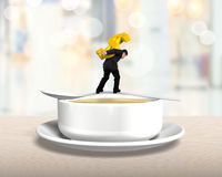 Man carrying dollar sign balancing on spoon with soup bowl Royalty Free Stock Photos