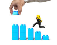 Man carrying dollar sign running bar graph block hand building Stock Photo