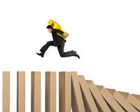 Man carrying dollar sign running on falling wooden dominos Royalty Free Stock Photo