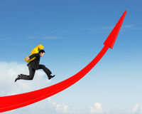 Man carrying dollar sign running on red arrow up graph Stock Photo