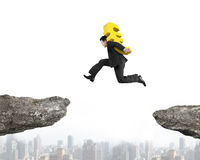 Man carrying euro sign jumping over two cliffs Stock Images
