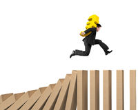 Man carrying Euro sign running on falling wooden dominos Royalty Free Stock Photos