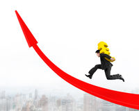 Man carrying Euro sign running on red arrow up graph Royalty Free Stock Image