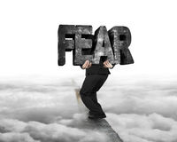 Man carrying fear concrete word on ridge with cloudy Stock Photography