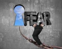 Man carrying fear word on chain toward keyhole with sky Stock Photos
