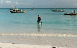 Man carrying fish on the African seashore Stock Images