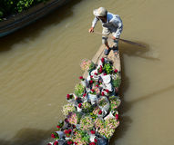 A man carrying flowers by boat in Ben Tre, Vietnam Royalty Free Stock Image