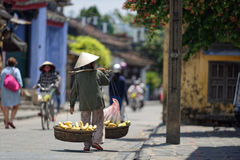Streets of Hoi An. Man carrying fruits among other locals and travelers walking on the street in Hoi An, Vietnam royalty free stock images