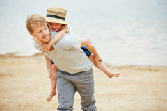 Man carrying girl piggyback on his back Royalty Free Stock Images