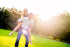 Man carrying girl piggyback in summer Stock Images
