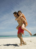 Man carrying girlfriend on back. Stock Photo