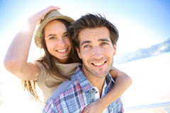 Man carrying girlfriend on his back on the beach Stock Images