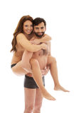 Man carrying girlfriend on his back. Royalty Free Stock Image