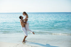 Man carrying girlfriend while standing at beach Royalty Free Stock Photo