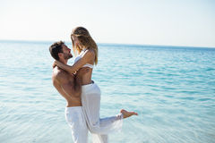 Man carrying girlfriend while standing on shore Royalty Free Stock Image