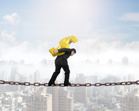 Man carrying golden dollar sign balancing on chain Stock Photography