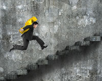 Man carrying golden dollar sign running on old concrete stairs Royalty Free Stock Image