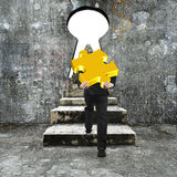 Man carrying golden jigsaw puzzle climbing concrete stairs towar Royalty Free Stock Photography