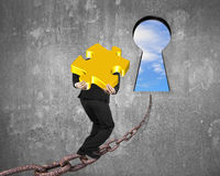 Man carrying golden puzzle on chain toward keyhole with sky Royalty Free Stock Photos