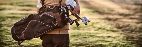 Man carrying golf bag while standing on field. Rear view royalty free stock photos