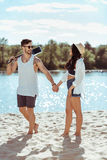 Man carrying guitar and holding hands with his girlfriend on sandy beach stock image