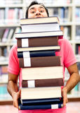Man carrying heavy books Stock Image