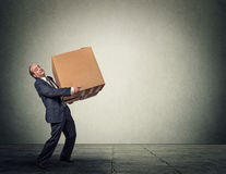 Man carrying heavy box. Man carrying large heavy box Royalty Free Stock Photography
