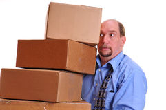 Man carrying heavy boxes hoping not to drop them royalty free stock photo