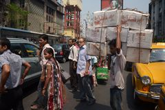 Man carrying heavy boxes on the street. Kolkata, India - March, 2014: Man carrying heavy boxes and crossing road with other people on pedestrian. Indian city Stock Photography