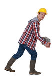 Man carrying heavy brick Royalty Free Stock Image