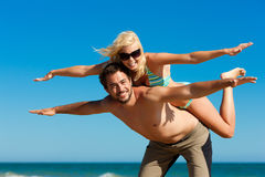 Man carrying his girl friend on the beach Stock Images