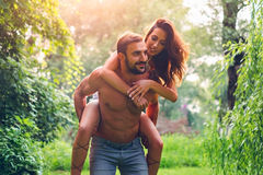 Man carrying his girl in nature Royalty Free Stock Photos