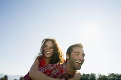 A man carrying his girlfriend on his back. Stock Images