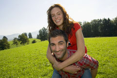 A man carrying his girlfriend on his back. Stock Photos