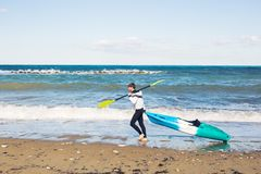 Man carrying his kayak along the shore. Royalty Free Stock Image