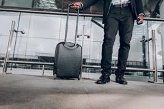 Man is carrying his luggage at the station. Ready for journey. Close up of male legs and suitcase. He is standing at the station and waiting for arrival Stock Photo
