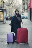 Man carrying his luggage on the street. Man with hat and luggage on the streets of Barcelona Stock Images