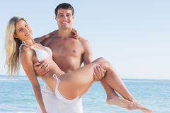 Man carrying his pretty girlfriend smiling at camera. At the beach Royalty Free Stock Photo