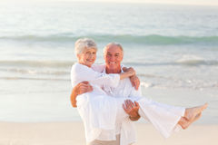 Man carrying his wife on the beach Royalty Free Stock Images