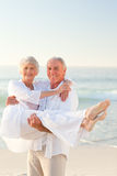 Man carrying his wife on the beach Royalty Free Stock Photo