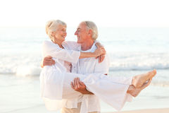 Man carrying his wife on the beach Stock Images