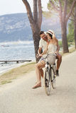 Man carrying his woman on a bike in the lake zone Royalty Free Stock Photography