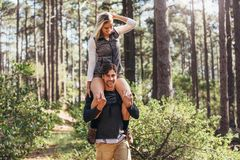 Man carrying his woman partner on his shoulders while trekking i Stock Photos